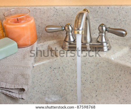 Typical bathroom sink with running water and soap, candle and cloth on the counter