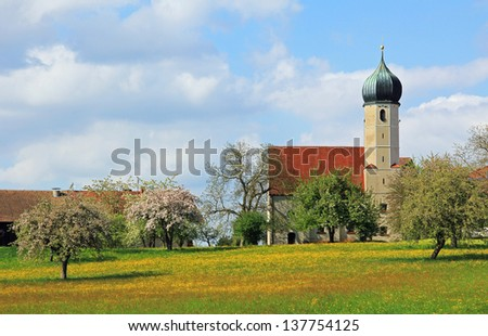 typical bavarian church with onion dome, fruit orchard, at springtime, german landscape - stock photo