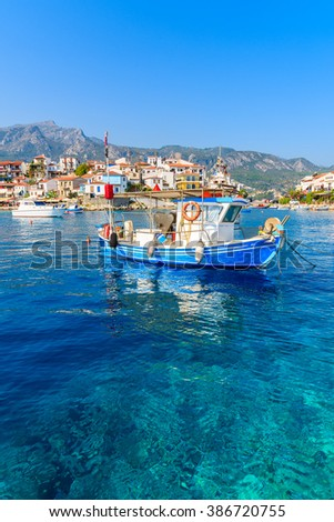 Typical blue and white colour fishing boat on azure crystal clear sea water in Kokkari port, Samos island, Greece