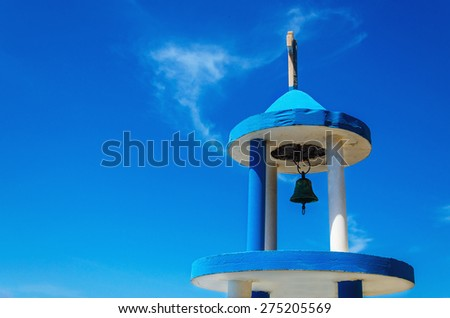 Typical blue-white church tower (steeple) with bell of greek church against blue sky - stock photo