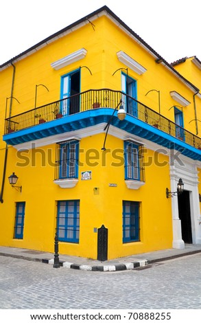 Typical bright yellow house with blue doors and windows in a corner in old Havana isolated on white - stock photo