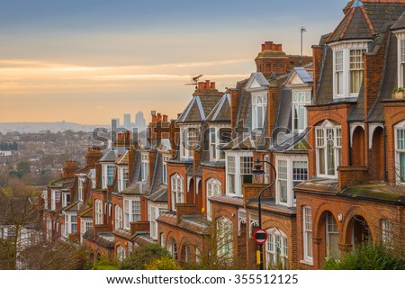 Typical British brick houses on a cloudy morning with sunrise and Canary Wharf at the background. Panoramic shot from Muswell Hill, London, UK - stock photo
