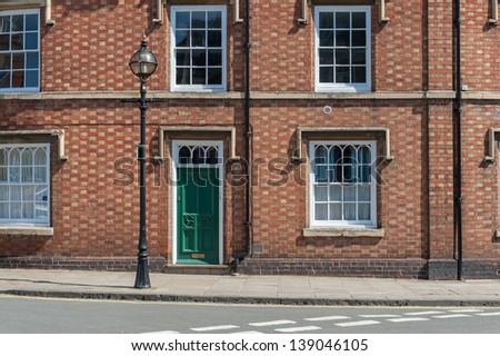 Typical british building with green door. - stock photo