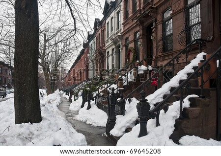 Typical brownstone row houses in Brooklyn. Street covered in snow - stock photo