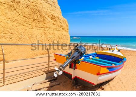 Typical colorful fishing boat on sandy Benagil beach in Algarve region, Portugal - stock photo
