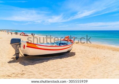 Typical colourful fishing boat on sandy beach in Armacao de Pera village, Algarve region, Portugal - stock photo