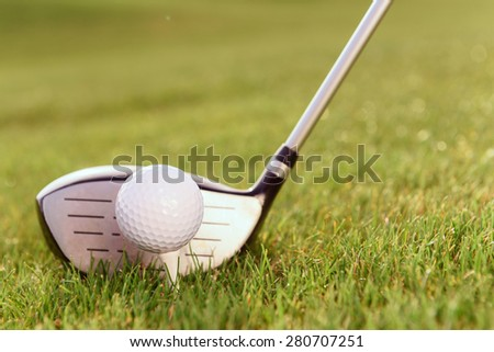 Typical combination. Close up of golf club and ball on tee put together on grass. - stock photo