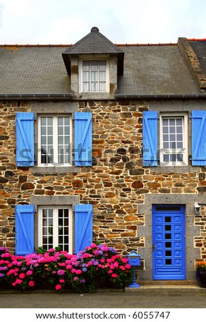 Typical country house with blue shutters in Brittany, France - stock photo