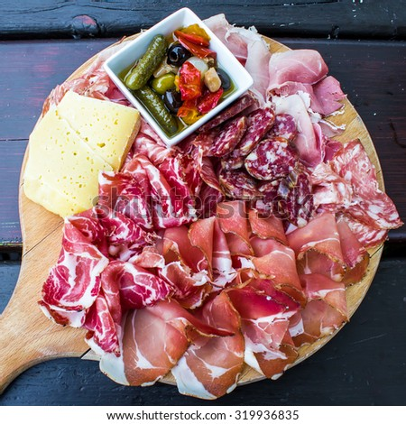 typical dish of Italian appetizer with salami, ham and cheese - stock photo