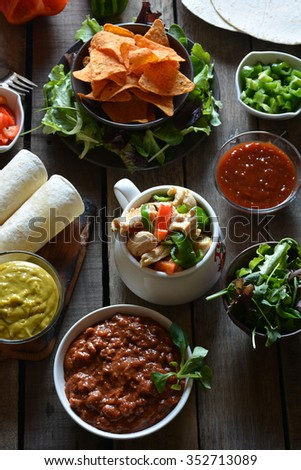typical dishes of mexico made guacamole, chili with meat, chicken, vegetables and nachos - stock photo