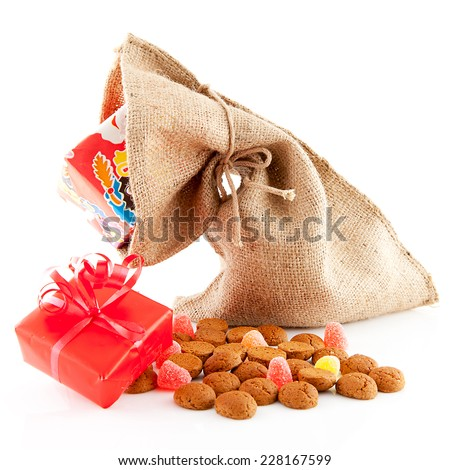 Typical Dutch celebration: Sinterklaas with surprises in bag and ginger nuts, ready for the kids in december. Isolated on white background - stock photo