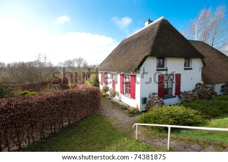 typical dutch house behind the dike along the Waal river - stock photo