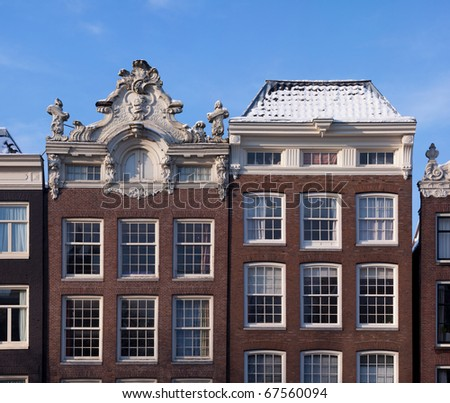 Typical Dutch houses in Amsterdam, the Netherlands alongside one of its famous canals. - stock photo