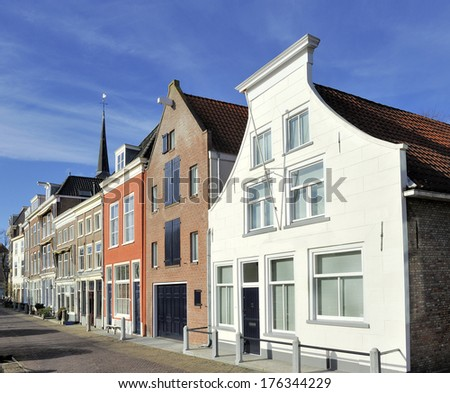 Typical Dutch houses in the old town of Delft at Kolk street. At the facade of the right white  house is a text that says that in the past there was a milk factory settled in the building. - stock photo
