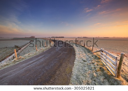 Typical Dutch landscape on a frosty morning at sunrise. This is part of the 13th century West-Frisian Circular Dyke in the northwest of The Netherlands. - stock photo