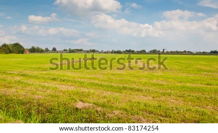 Typical Dutch landscape with grass and a small village - stock photo
