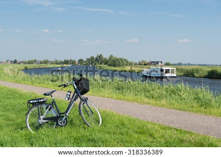 Typical Dutch landscape with river water and bike - stock photo