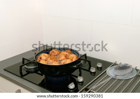 Typical Dutch oliebollen in the pan with hot oil - stock photo