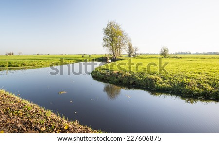 Typical Dutch polder landscape with a stream with a mirror smooth water surface on a sunny and windless day in the fall season. - stock photo
