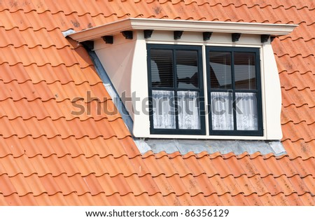 Typical Dutch roof with dormer and squared windows - stock photo