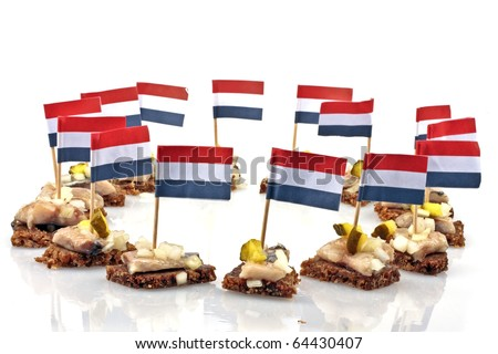Typical dutch: Rye bread with raw herring and onions with the dutch flag - stock photo