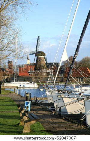 Typical Dutch view. Marine with sailboat and old, traditional windmill in Sloten, small town in Netherlands. - stock photo