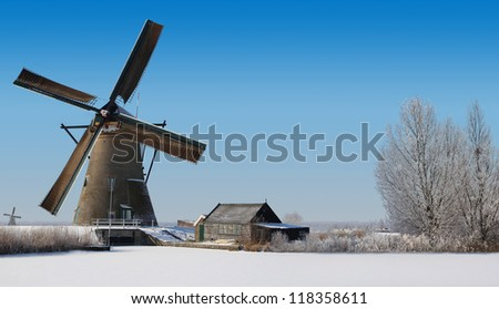 Typical dutch windmill and an old shack in the winter - stock photo