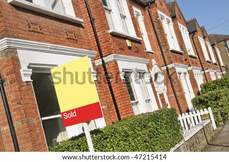"""Typical English home with a """"Sold"""" sign. - stock photo"""