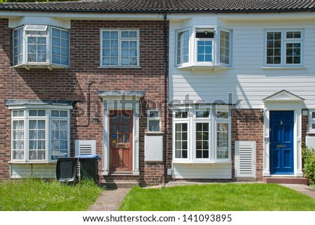 Typical English Terraced Houses in South East of the UK. A well-maintained and a neglected houses side by side. - stock photo