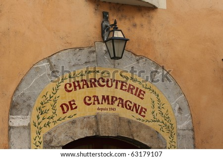 Typical entrance to a butcher's shop in southern France. Shop sign made out of several tiles. - stock photo