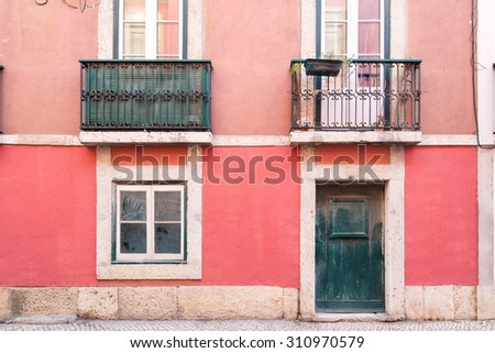 Typical exterior of old houses in narrow street in Bairro Alto in Lisbon, capital of Portugal, leading to a colorful composition - stock photo