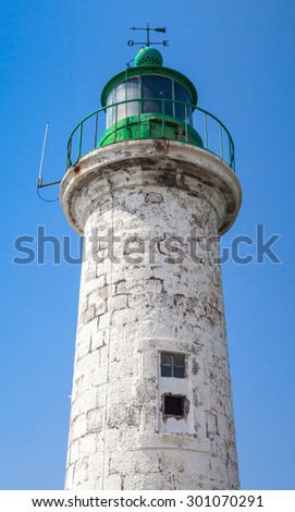 Typical for Mediterranean Sea coasts old lighthouse over blue sky background. White round tower made of stone with green top - stock photo