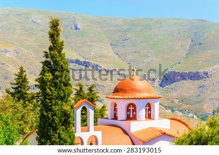 Typical Greek church in mountains with cyprus in the garden, southern Greece - stock photo