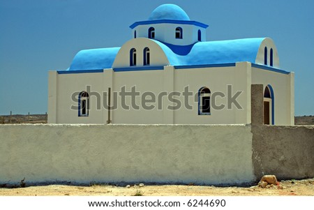 Typical Greek church - white walls and a blue cupola - stock photo