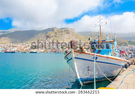 Typical Greek Fishermens' boat standing in harbour with port building in backgound on Greek Island, southern Greece - stock photo