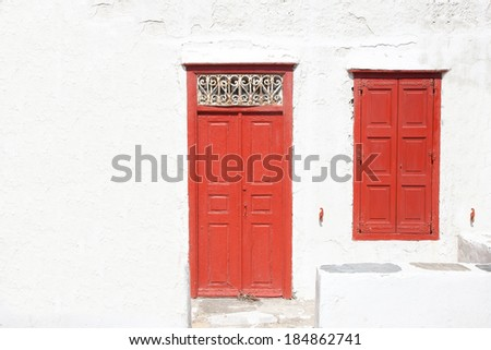 Typical Greek house with whitewashed walls and a colorful red door with matching closed window shutters in sunshine, architectural background - stock photo