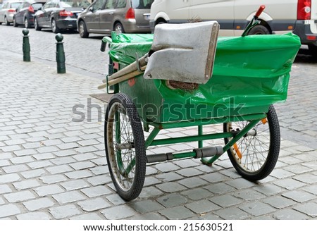Typical green pushcart of municipal street cleaning service worker of Brussels with ancient coat of arms of the city - stock photo