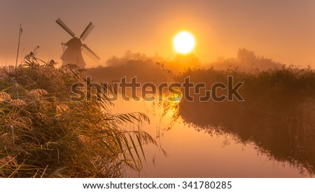 Typical historic windmill in a polder wetland on a cool colored foggy september morning in the Netherlands - stock photo