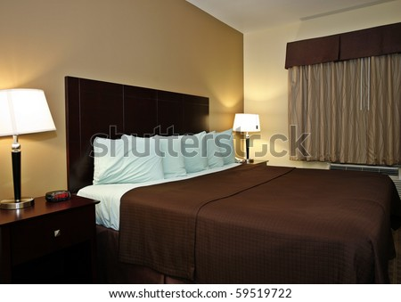 Typical hotel room with queen size bad - stock photo