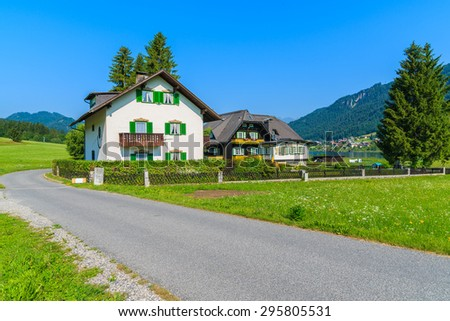 Typical houses along road in countryside landscape of Alps Mountains in summer landscape of Weissensee lake, Austria - stock photo