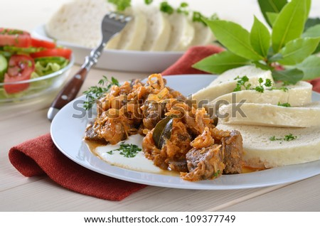 Typical Hungarian goulash (pork and beef) with pickled white cabbage (sauerkraut) and dumplings in a napkin - stock photo