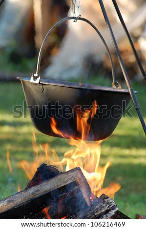Typical Hungarian Guly�¡s (Soup) is jut cooking in Cauldron on Campfire - stock photo