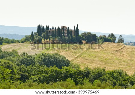 Typical Italian farm lined with cypress trees - stock photo