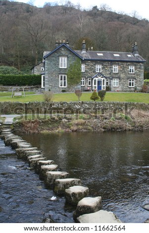 Typical Lake District house, with stepping stones over the river Rothay, Cumbria.