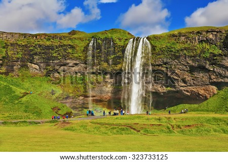 Typical landscape for the summer in Iceland. At the foot of the waterfall Seljalandsfoss crowds of tourists - stock photo