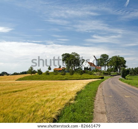 Typical landscape of funen with white church - stock photo