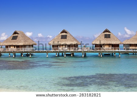 typical landscape of tropical islands - huts, wooden houses over water - stock photo