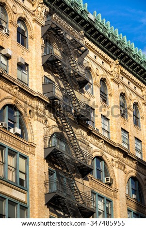 Typical late 19th century Soho brick building with fire escape, ornate facade and copper cornice. Manhattan, New York City - stock photo