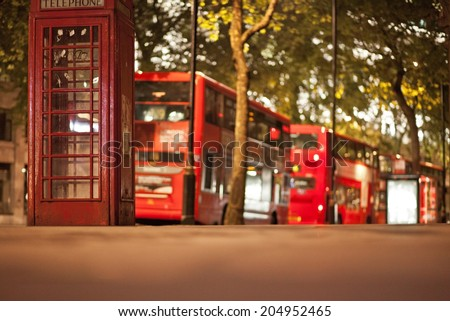 Typical London scene at night with phone booth in front and double deckers in background. Short depth of field, focus on phone booth. - stock photo