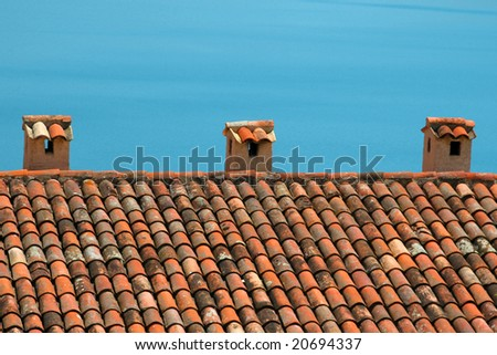 Typical mediterranean style roof with the blue ocean as a background. - stock photo